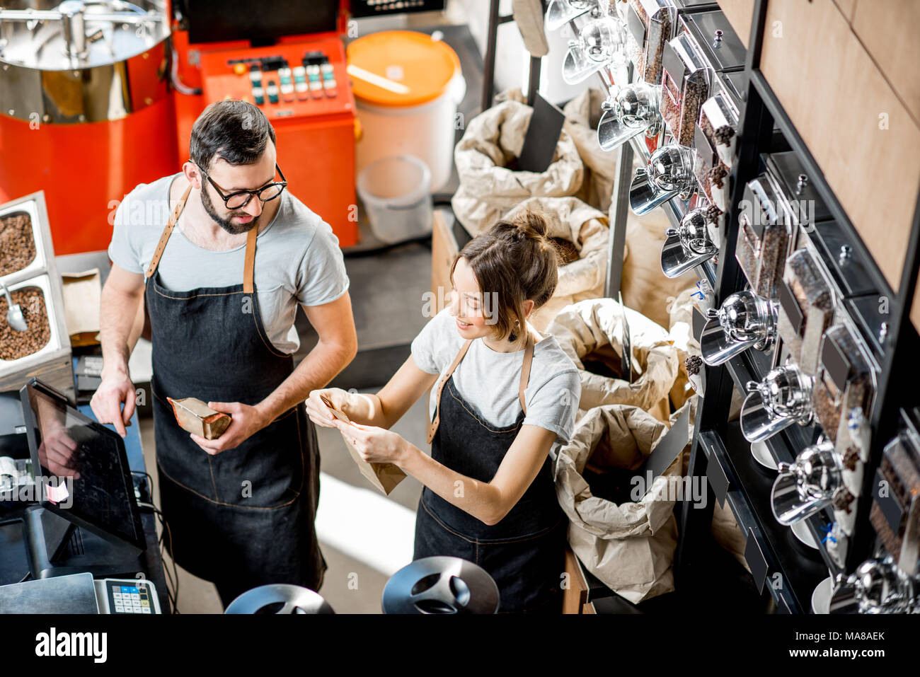 Two sellers in uniform filling and weighing bags with coffee in the coffee store. View from above - Stock Image