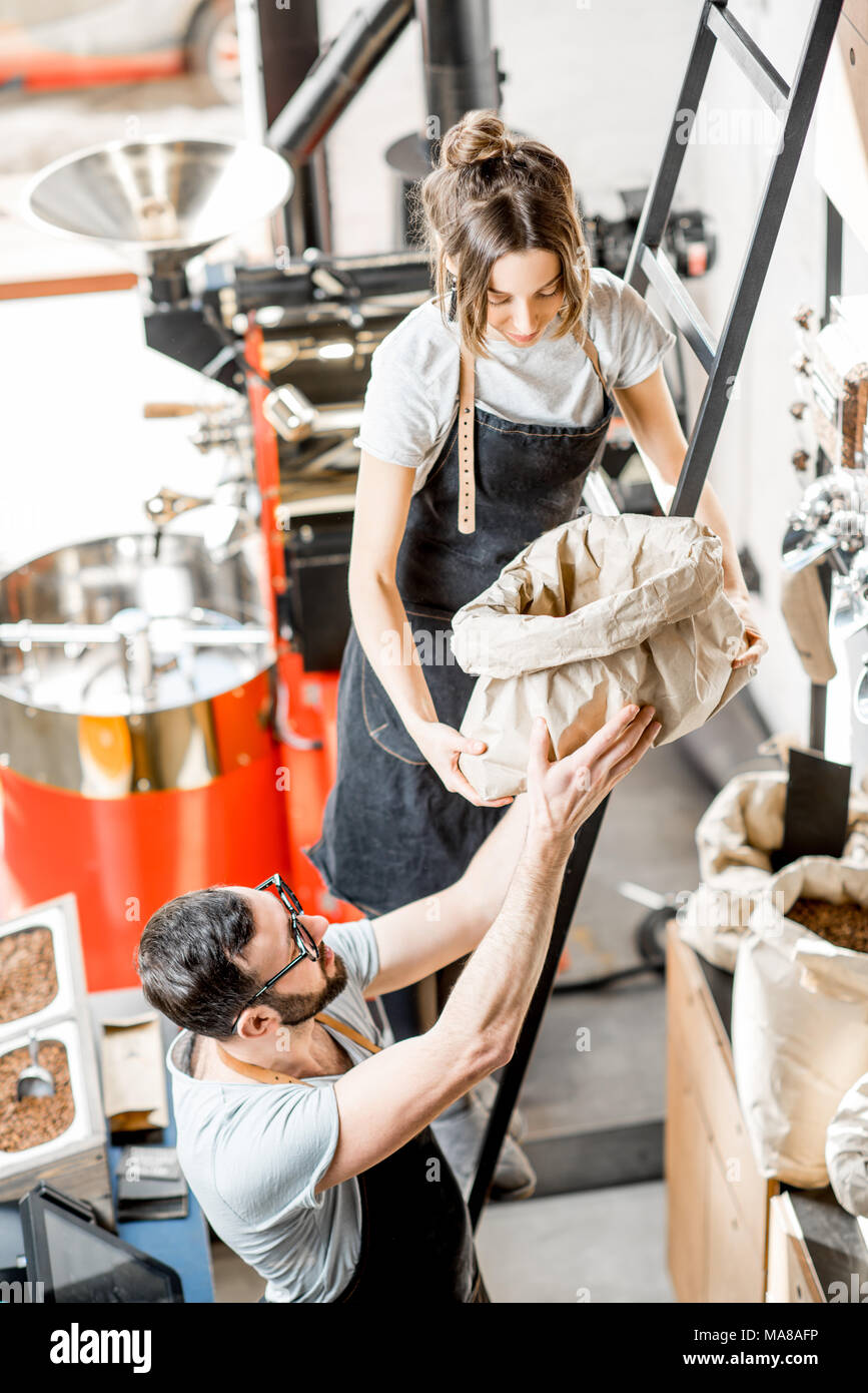 Two sales persons working with coffee in the coffee shop with roaster machine on the background - Stock Image