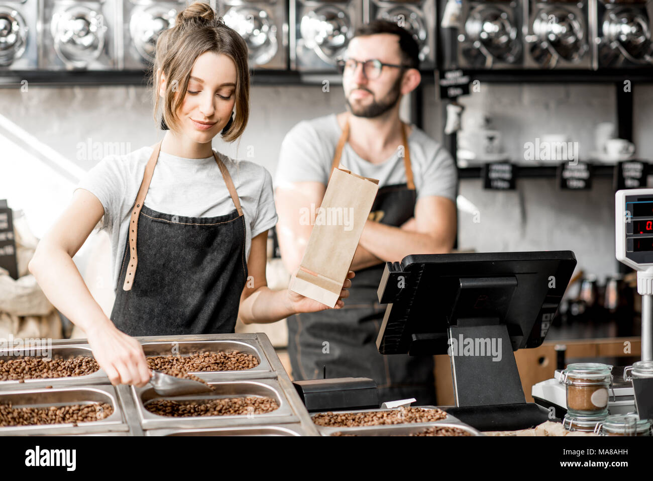 Woman seller filling paper bags with coffee beans while working in the coffee store - Stock Image