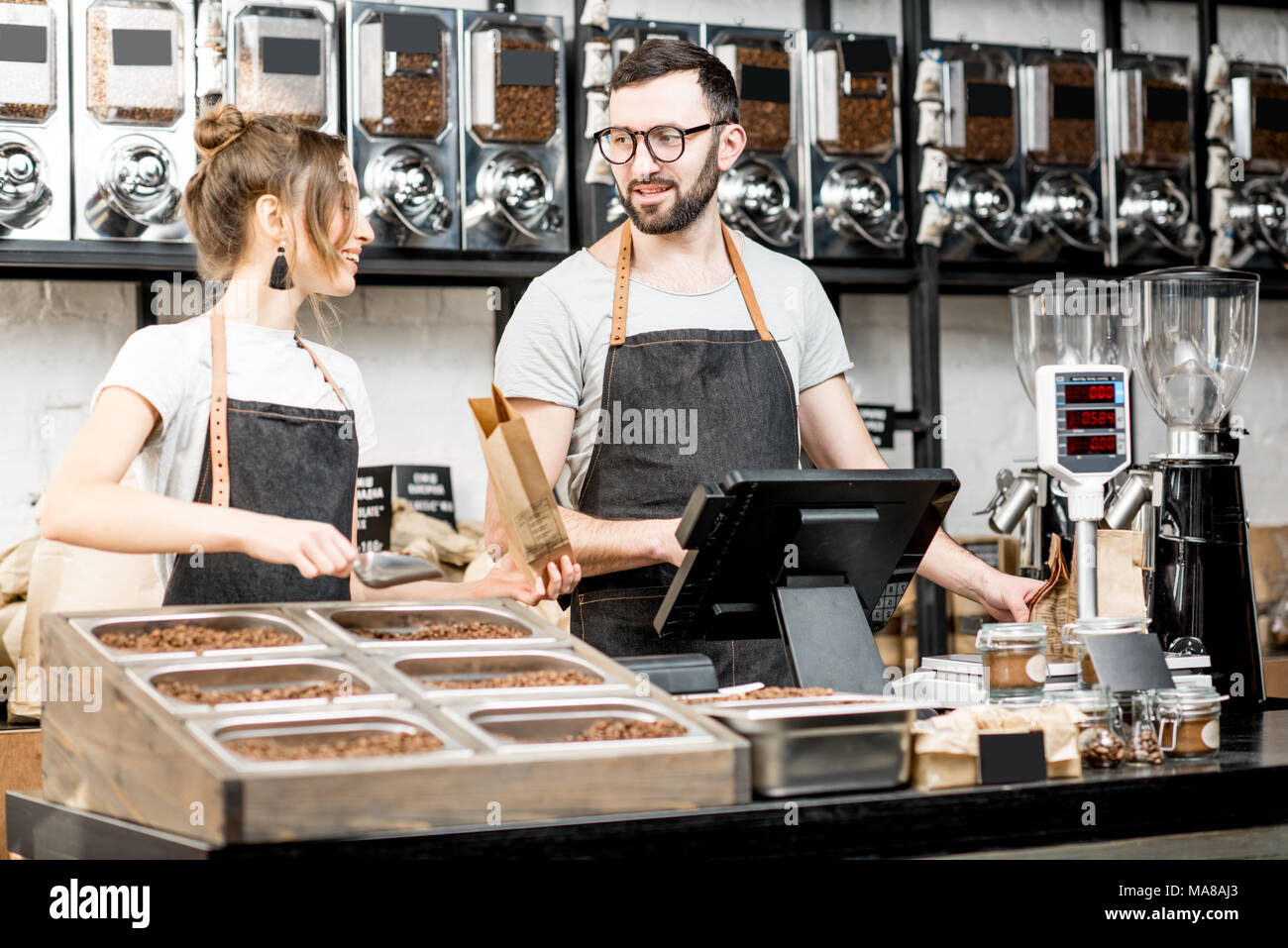 Two sellers in uniform filling bags with coffee beans while working in the coffee store - Stock Image