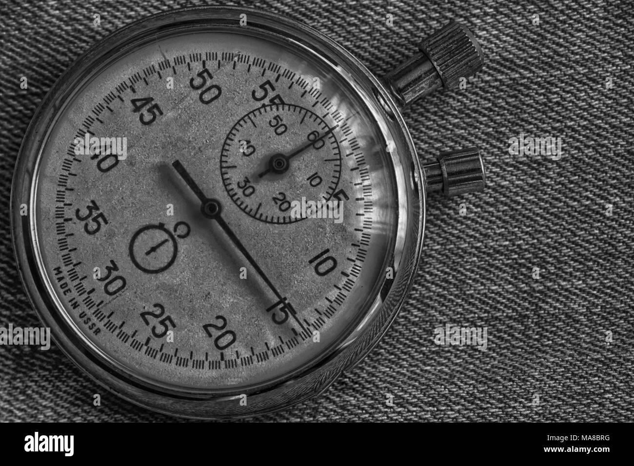 Stopwatch, on worn denim background, value measure time, old