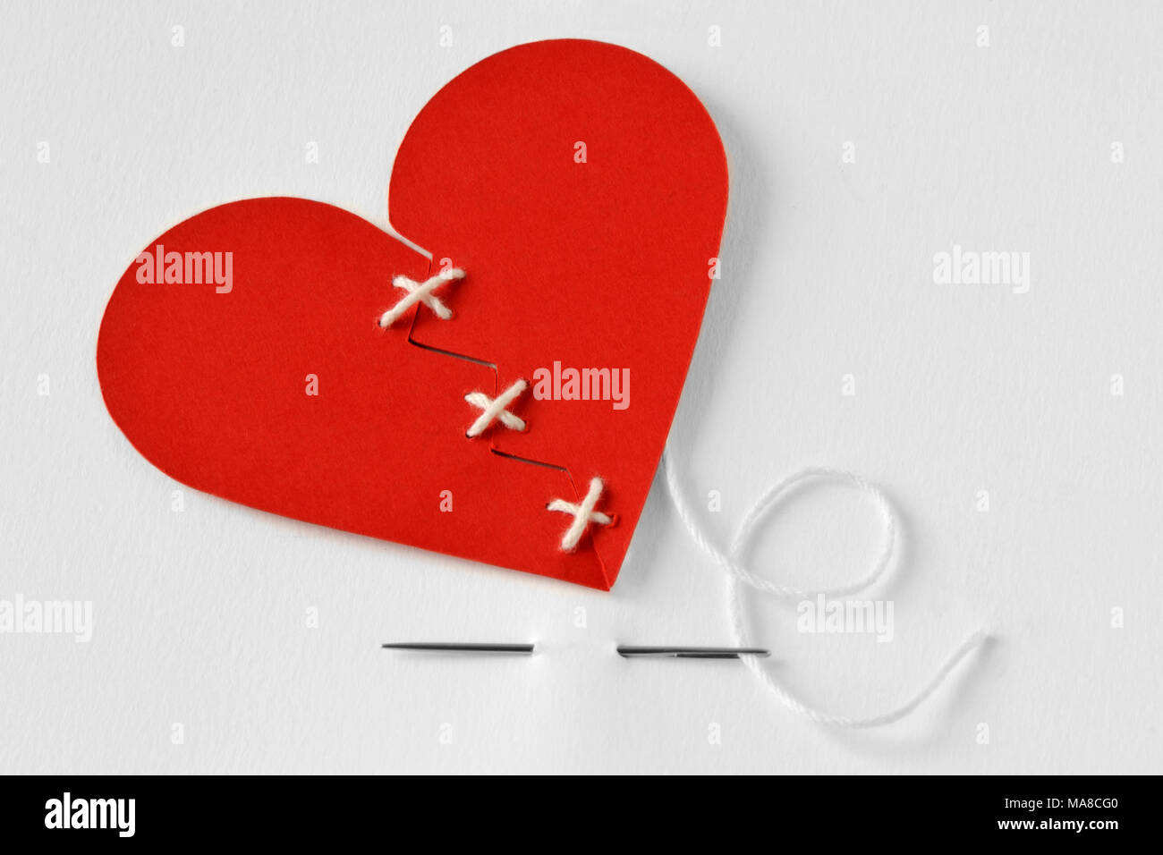 Paper broken heart sewn with needle and thread - Love troubles concept - Stock Image