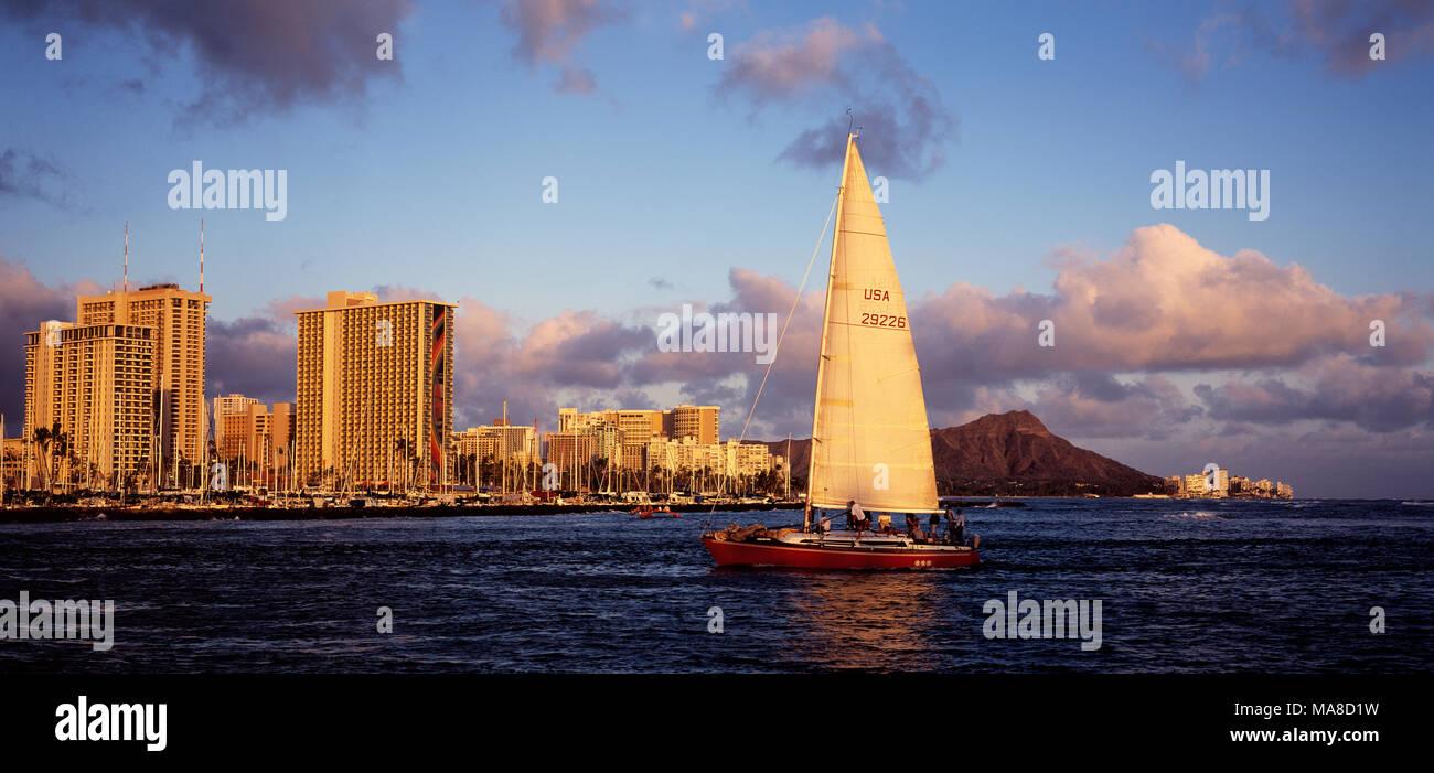 Side view of yacht with panoramic view of Waikiki, Honolulu, Hawaii. Stock Photo