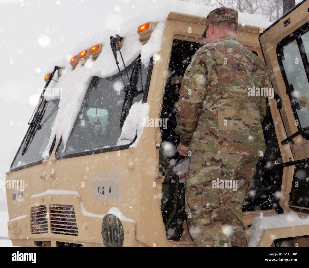 A New York Army National Guard Soldier from the 42nd Combat Aviation Brigade based in Latham, NNew York prepares his vehicle for missions as a massive snow storm hits New York, March 14, 2017. () Stock Photo