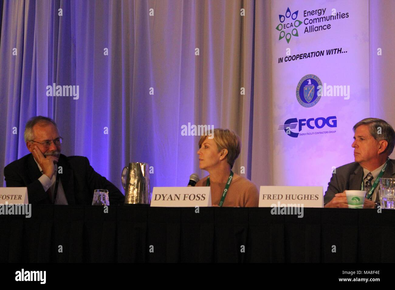 Three panel members, including Dyan Foss and Fred Hughes, seated behind a table at the United States Department of Energy (DOE) 2016 National Cleanup Workshop, held in cooperation with the Energy Communities Alliance (ECA) and FCOG, September 14-15, at the Hilton Alexandria Mark Center in Alexandria, Virginia, Image courtesy US Department of Energy, September, 2016. () - Stock Image