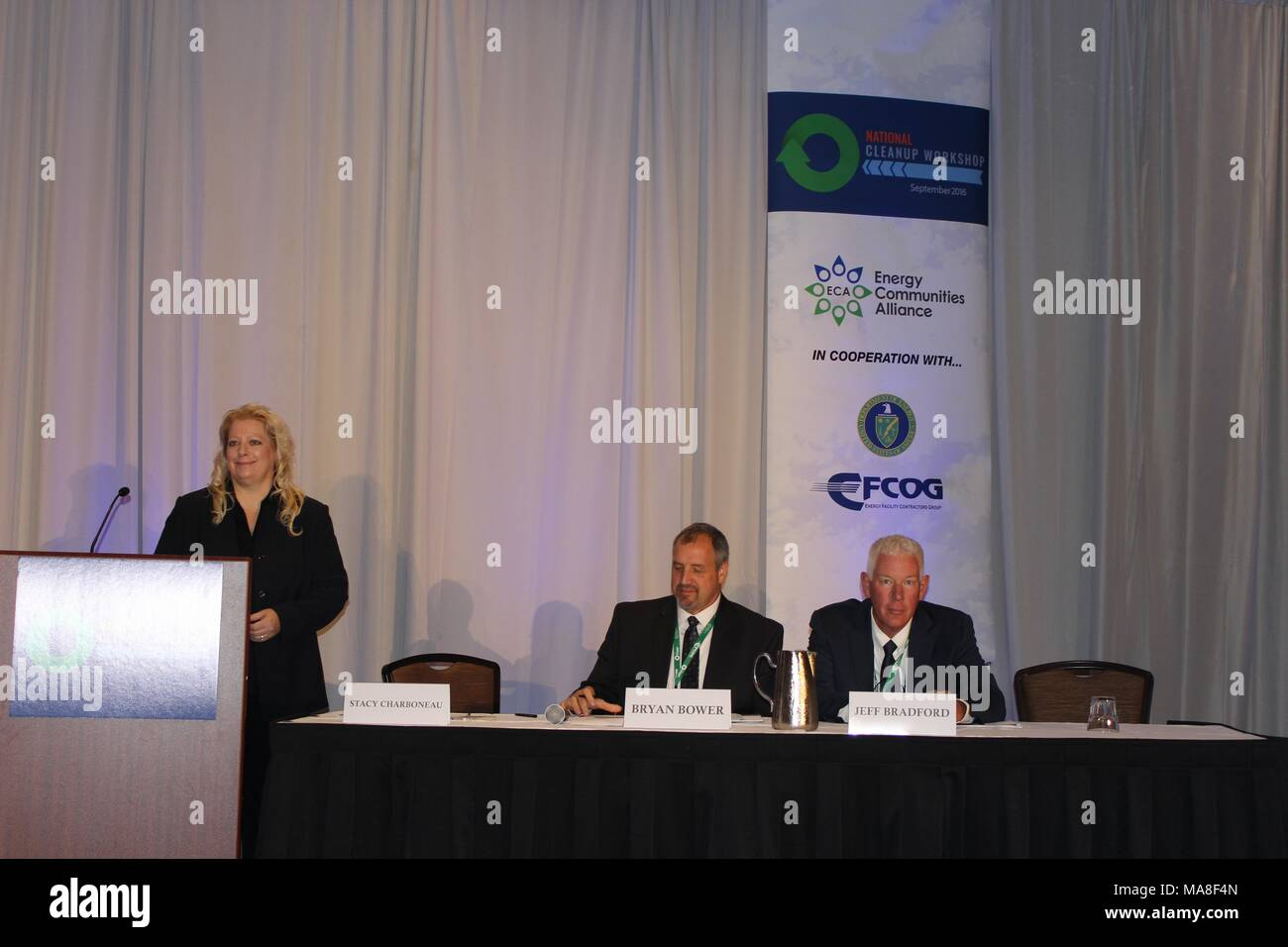 Stacy Charboneau standing behind a podium, with panel members Bryan Bower, and Jeff Bradford, seated at the table next to her, at the United States Department of Energy (DOE) 2016 National Cleanup Workshop, held in cooperation with the Energy Communities Alliance (ECA) and FCOG, September 14-15, at the Hilton Alexandria Mark Center in Alexandria, Virginia, Image courtesy US Department of Energy, September, 2016. () - Stock Image