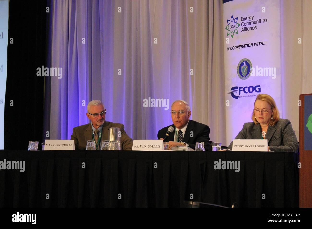 Three members of a panel, including Mark Lindholm, Kevin Smith, and Peggy McCullough, seated behind a long, black skirted table, at the United States Department of Energy (DOE) 2016 National Cleanup Workshop, held in cooperation with the Energy Communities Alliance (ECA) and FCOG, September 14-15, at the Hilton Alexandria Mark Center in Alexandria, Virginia, Image courtesy US Department of Energy, 2016. () - Stock Image
