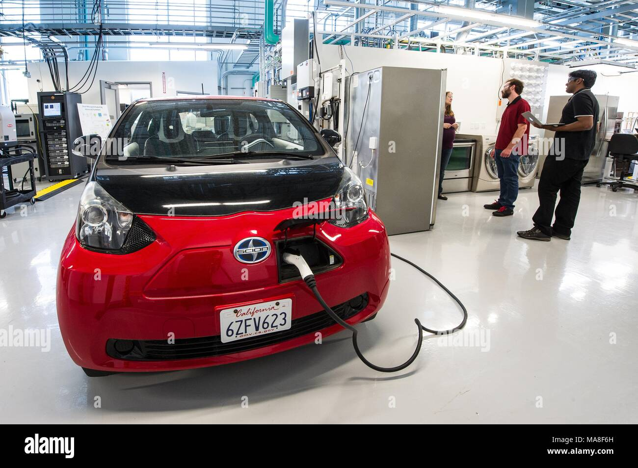 Three National Renewable Energy engineers work on the Electric Vehicle Supply Equipment (EVSE) and PV inverter as part of a 'smart-home-in-the-loop experiment, ' using a red, Toyota Scion, electric car, parked in a laboratory, at the Systems Performance Lab at the Energy Systems Integration Facility (ESIF), image courtesy of the US Department of Energy, July 11, 2016. () Stock Photo