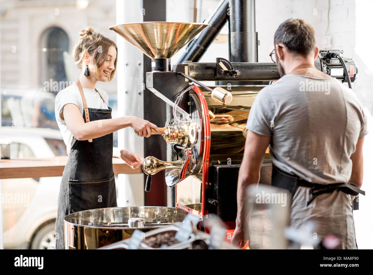 Man and woman in uniform working with roaster machine roasting coffee beans at the cafe - Stock Image