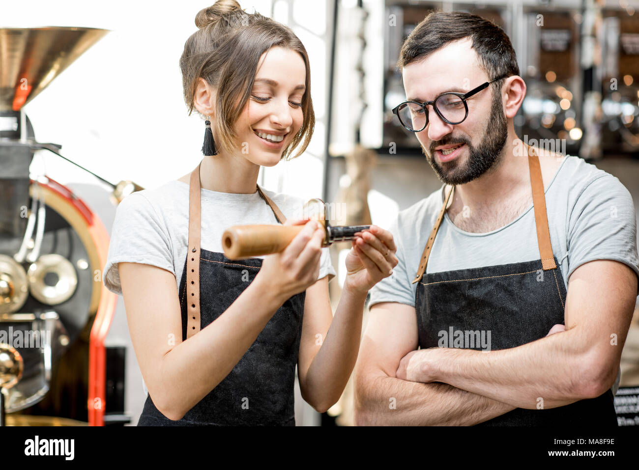 Couple of baristas in uniform checking the quality of roasted coffee beans standing near the roaster machine - Stock Image