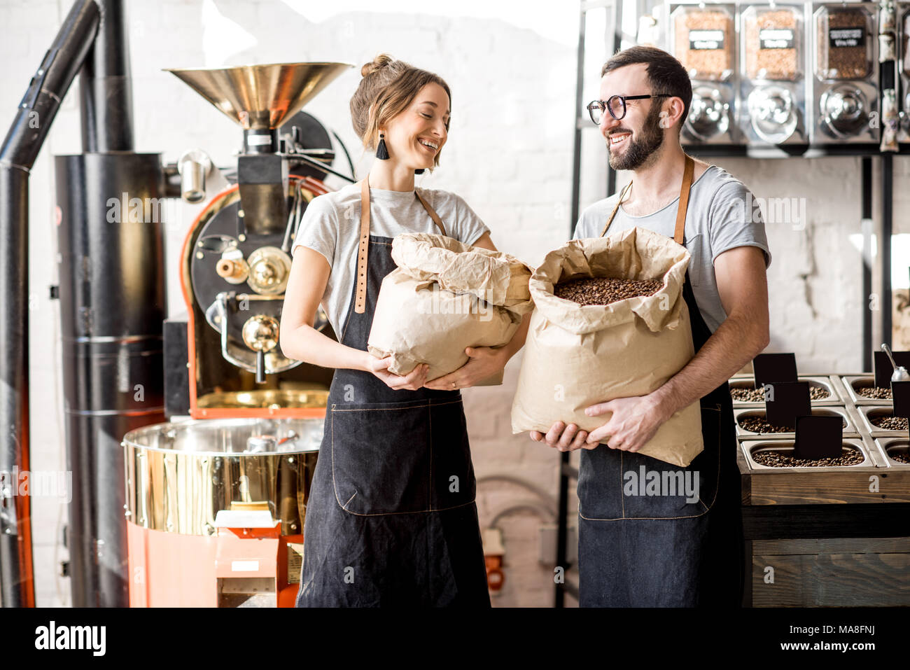 Portrait of a two happy baristas in uniform standing with bags full of coffee beans at the coffee store - Stock Image