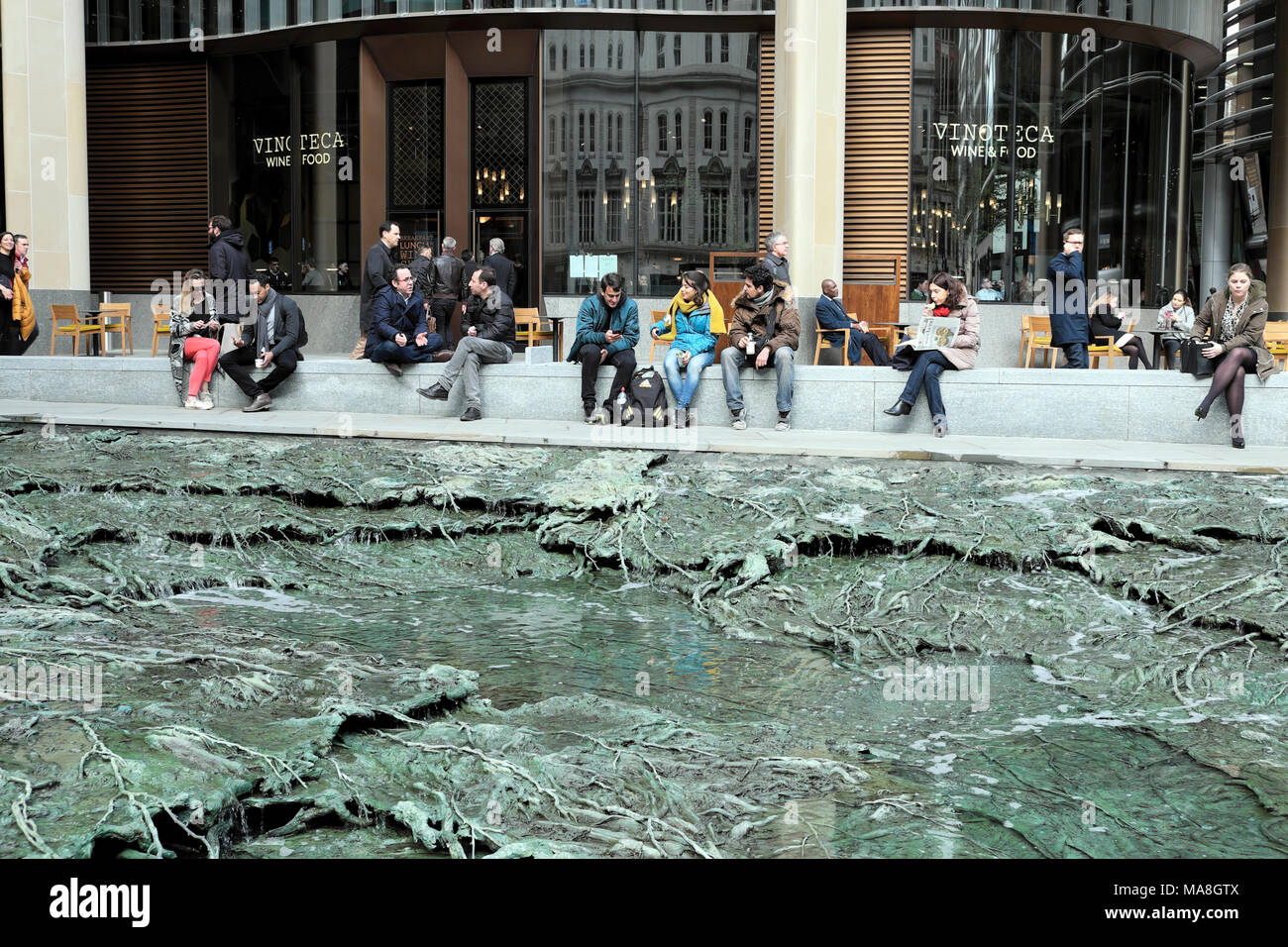 People sitting by 'Forgotten Streams' sculpture by artist Cristina Iglesias at the Bloomberg Headquarters building in City of London UK   KATHY DEWITT - Stock Image
