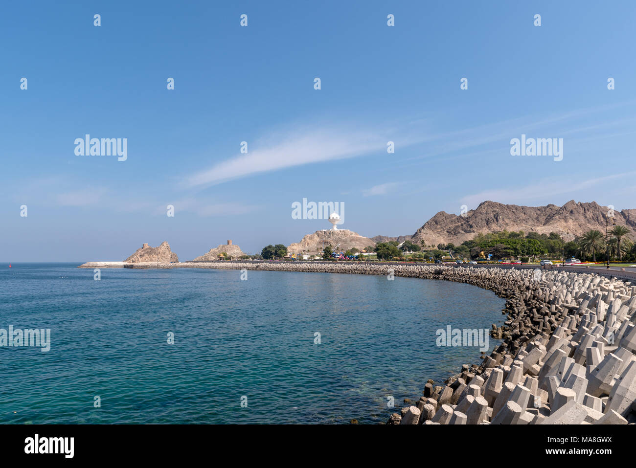 Coastline of Mutrah (old Muscat) in Oman with Riyam park, old watchtowers and breakwater visible - Stock Image
