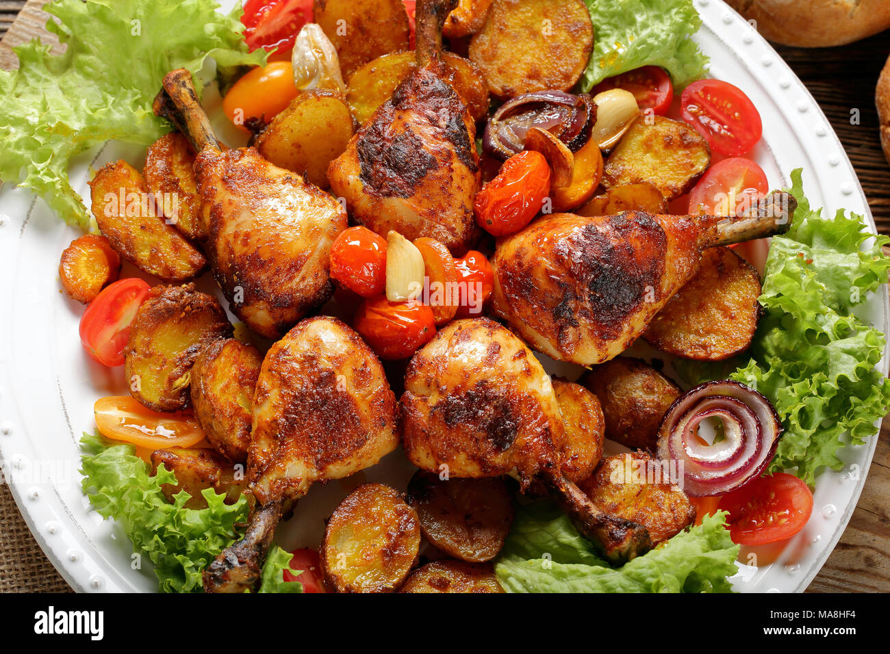 Roasted Chicken Legs With Baked Potato On The Plate Stock Photo