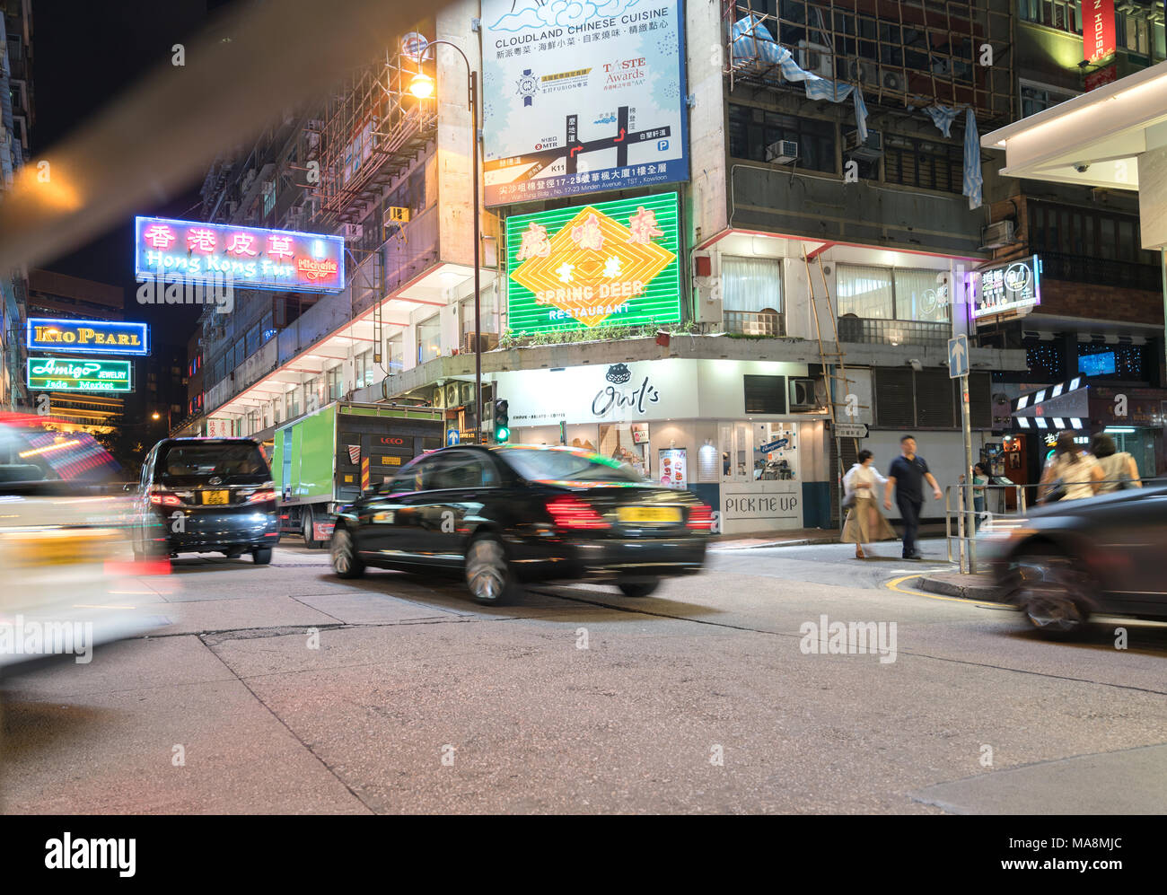 KOWLOON, HONG KONG - SEPTEMBER 18 2017; Bright neon signs dominate in long exposure night scene typically Asian downtown city corner street blurred pe - Stock Image