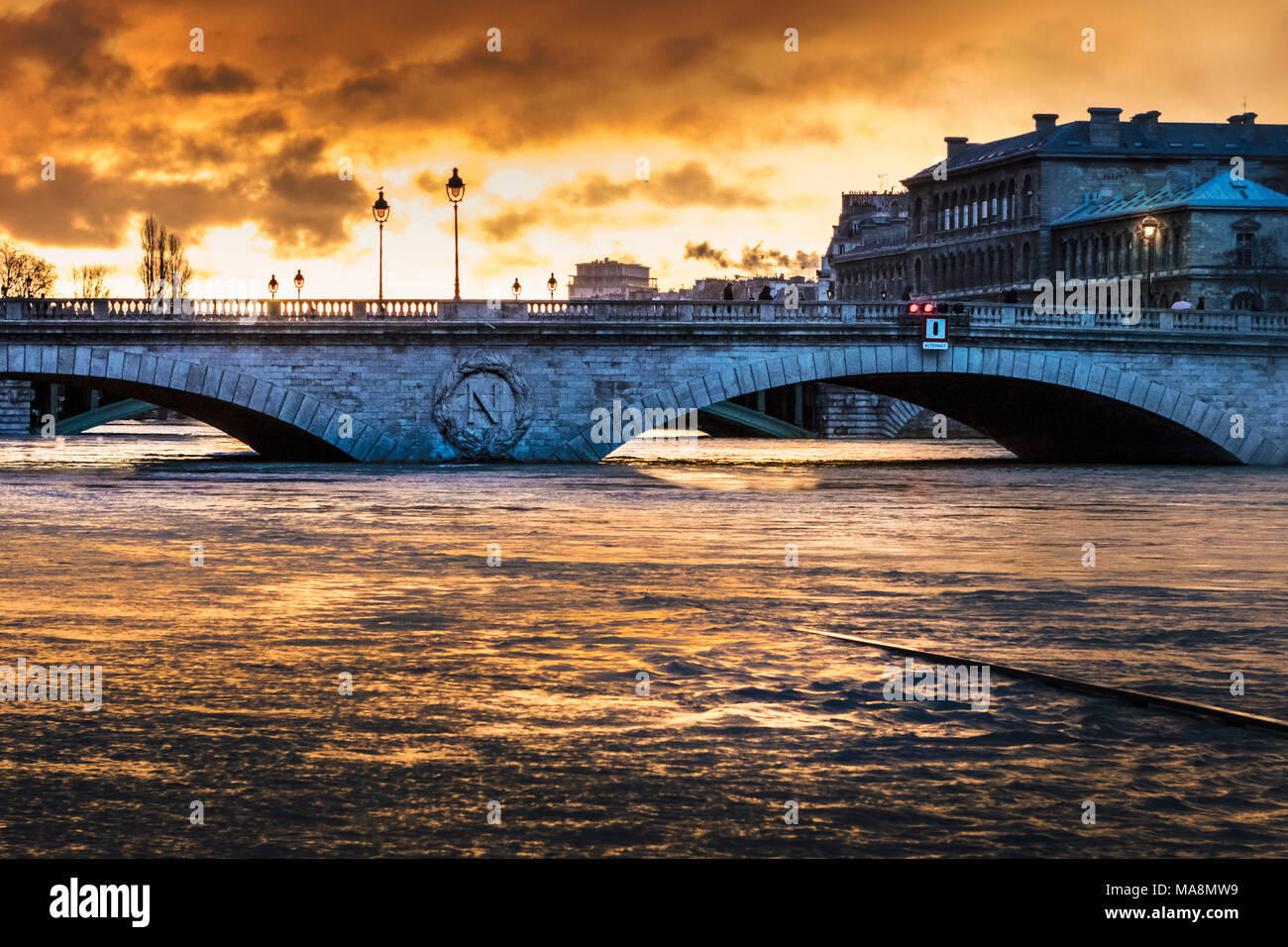 Pont au Change at sunrise with reflection of sky on the swollen Seine surging over submerged road during the Paris flood of January 2018 - Stock Image