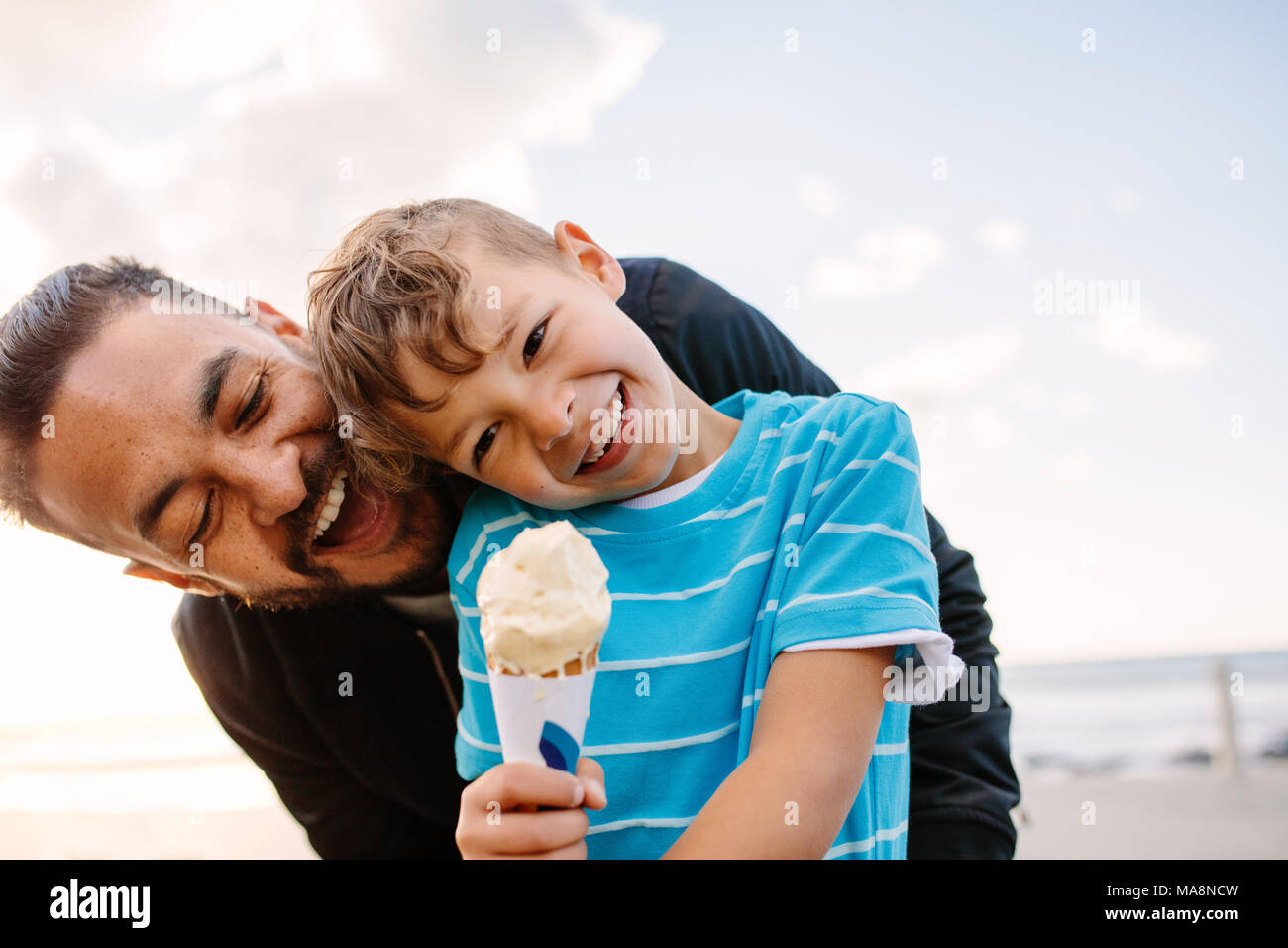 Boy eating an ice cream standing near seafront with his father. Little boy holding an ice cream cone while his father playfully tries to eat it from b - Stock Image