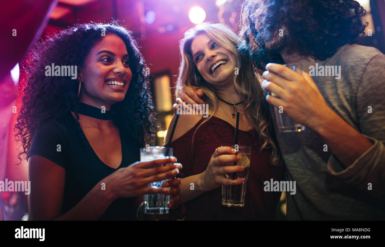 Happy young women partying friends at bar. Group of friends having a good time at nightclub. - Stock Image