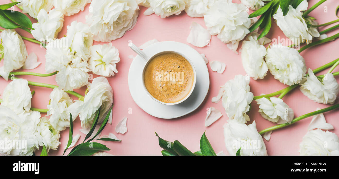 Cup of coffee and white ranunculus flowers on pink background - Stock Image