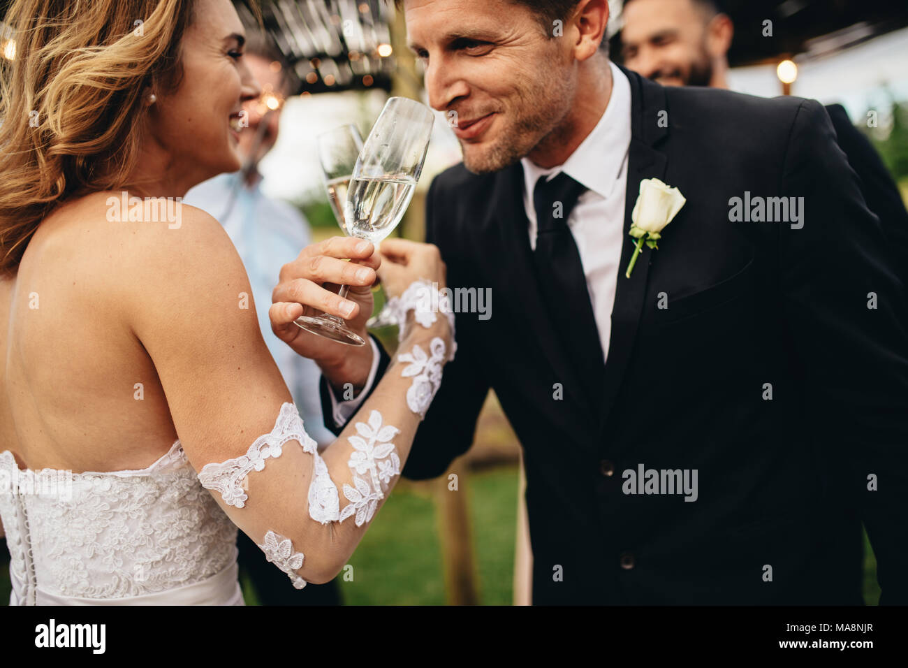Newlyweds clinking glasses and enjoying romantic moment together at wedding reception outside. Bride and groom drinking champagne at wedding party. - Stock Image