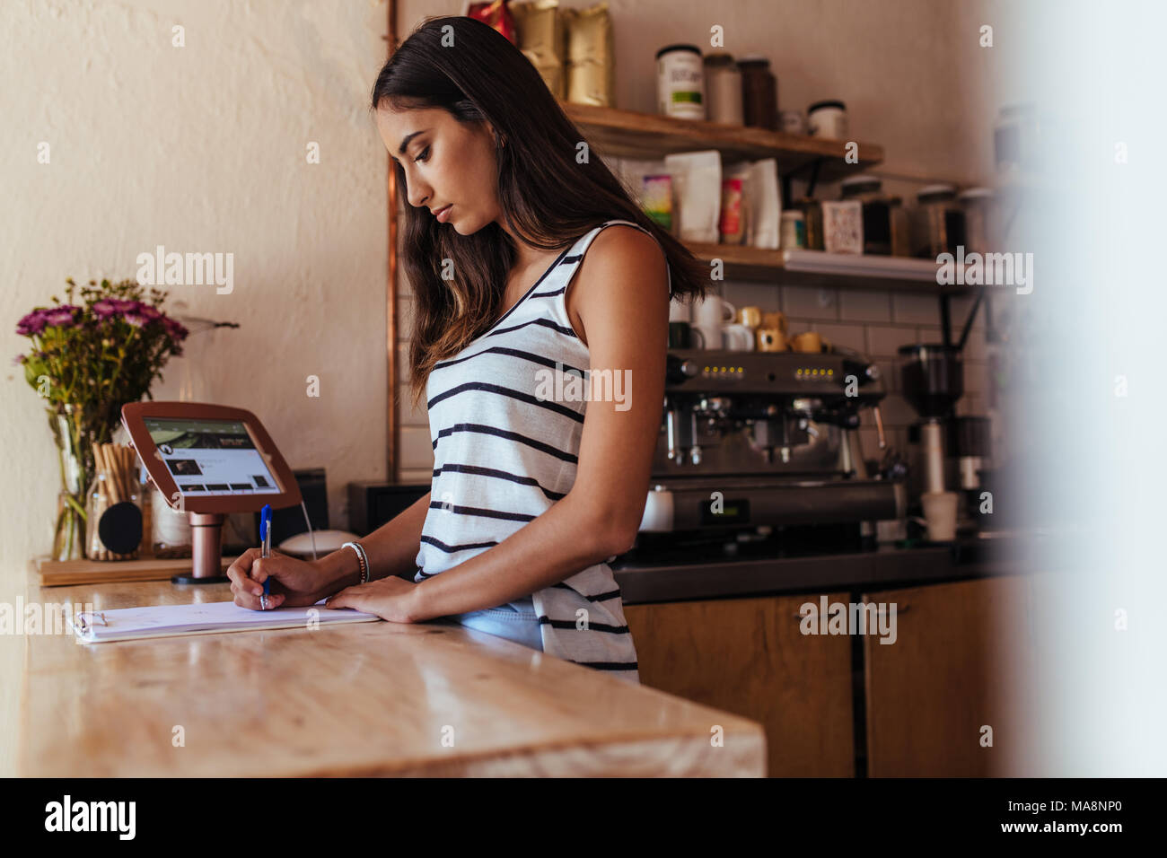 Woman standing at the billing counter of her cafe noting orders. Restaurant owner making notes standing at the billing counter. - Stock Image