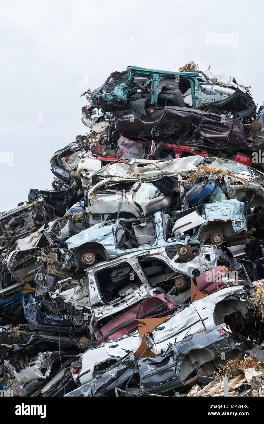 Dumping ground. Scrap metal heap. Compressed crushed cars is returned for recycling. Iron waste ground in the industrial area. Stacked automobile - Stock Image