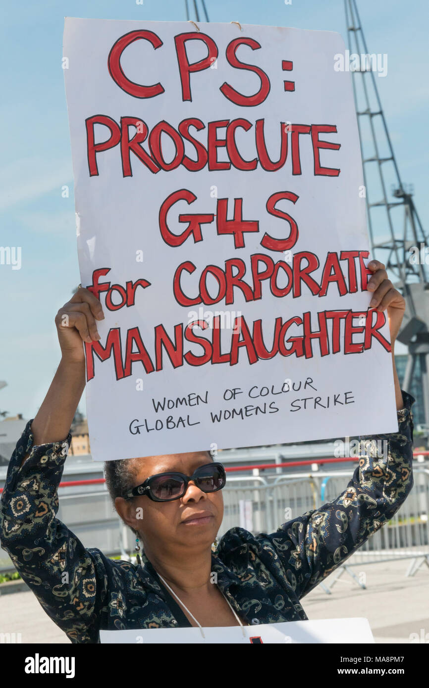 A woman from Women of Colour in the Global Womens Strik holds up a poster 'CPS: Prosecute G4S for Corporate Manslaughter' at Stop 4S protest outside G4S AGM at Excel London. Stock Photo