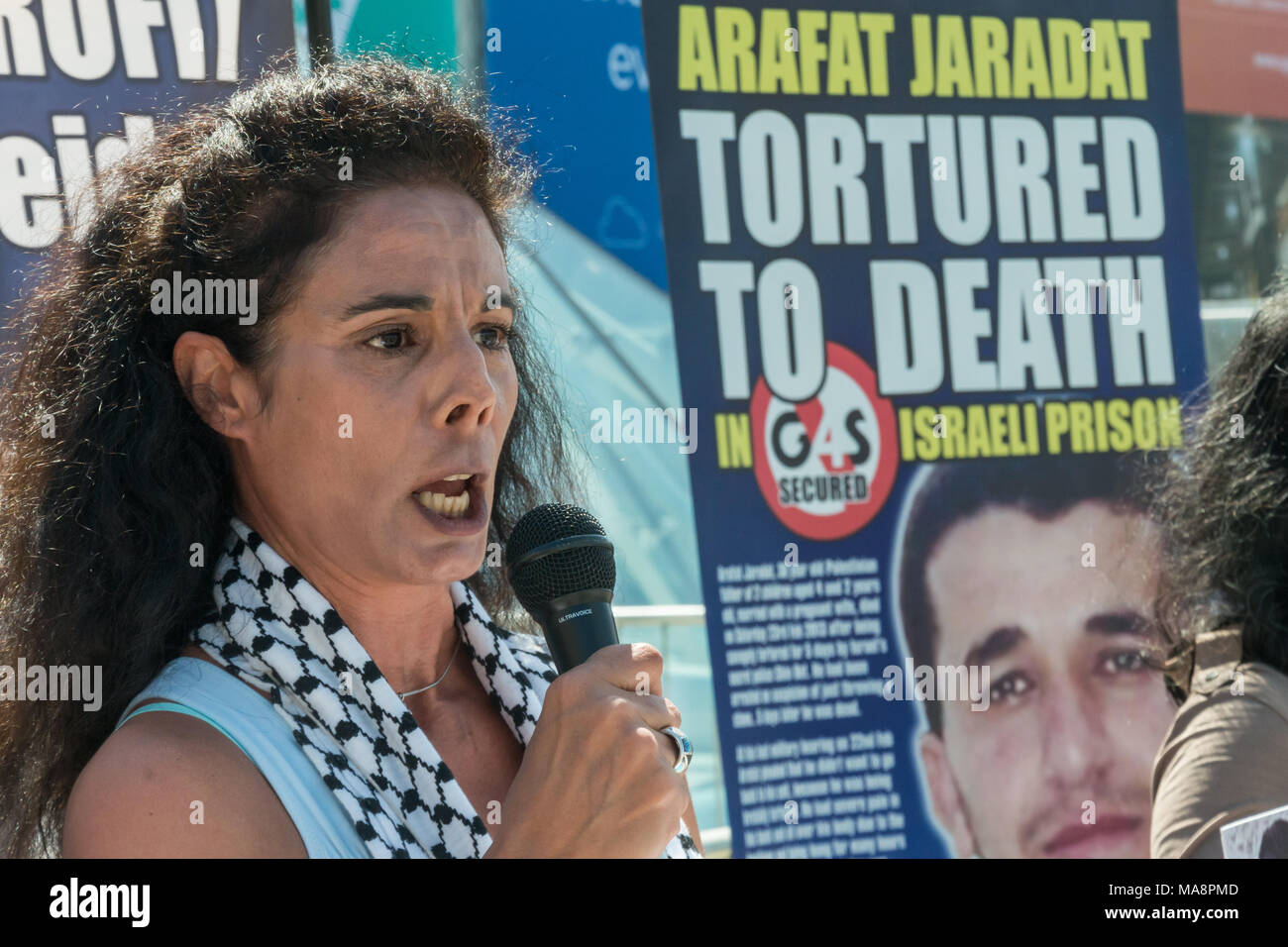 A woman reads a scathing account of the human rights abuses by Israeli forces, aided by Ga4S at the sotp Stop 4S protest outside G4S AGM at Excel London. Stock Photo