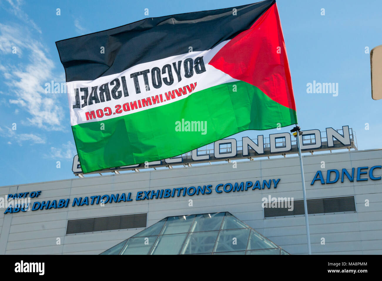 A Palestinian flag from Inminds with the message 'Boycott Israel' flying in front of Excel London at Stop 4S protest outside G4S AGM. The centre is owned by the Abu Dhabi National Exhibitions Company ADNEC. - Stock Image
