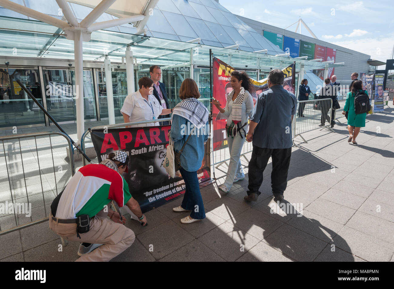 Excel staff argue with Inminds protesters who are putting up banners on the barriers outside Excel London at the Stop G4S protest outside G4S AGM. Inminds protest regularly outside the G4S offices in Victoria St. Stock Photo