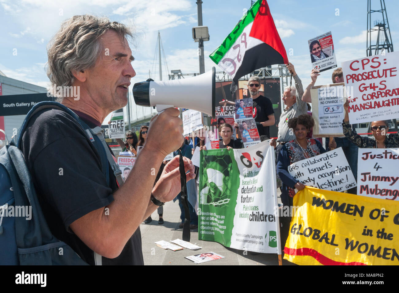 Protesters at Stop 4S protest outside G4S AGM at Excel London call for an end to immigration detention and human rights abuses in immigration detention centres and support for Israeli military and prison system by G4S Stock Photo
