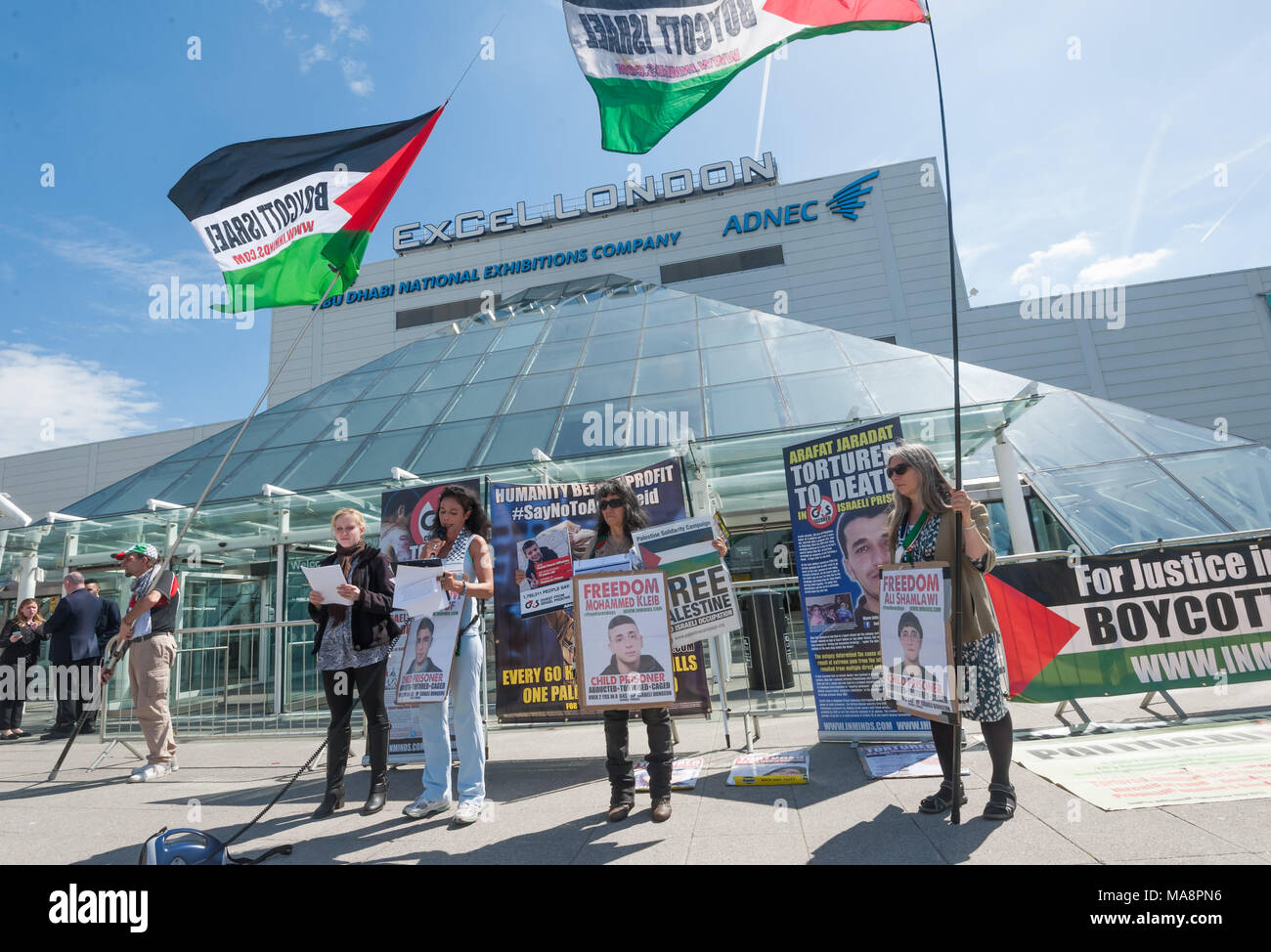 Inminds protesters with 'Boycott Israel' flags give a presentation outside the Excel Centre about human rights abuses by the Israeli government, aided by G4S, at Stop 4S protest outside G4S AGM at Excel London. Stock Photo