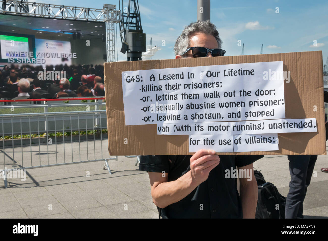 A man holds a poster listing a few of the faults of G4S, including killing prisoners, letting them escape, sexually abusing them and more at Stop G4S protest outside G4S AGM at Excel London. Stock Photo