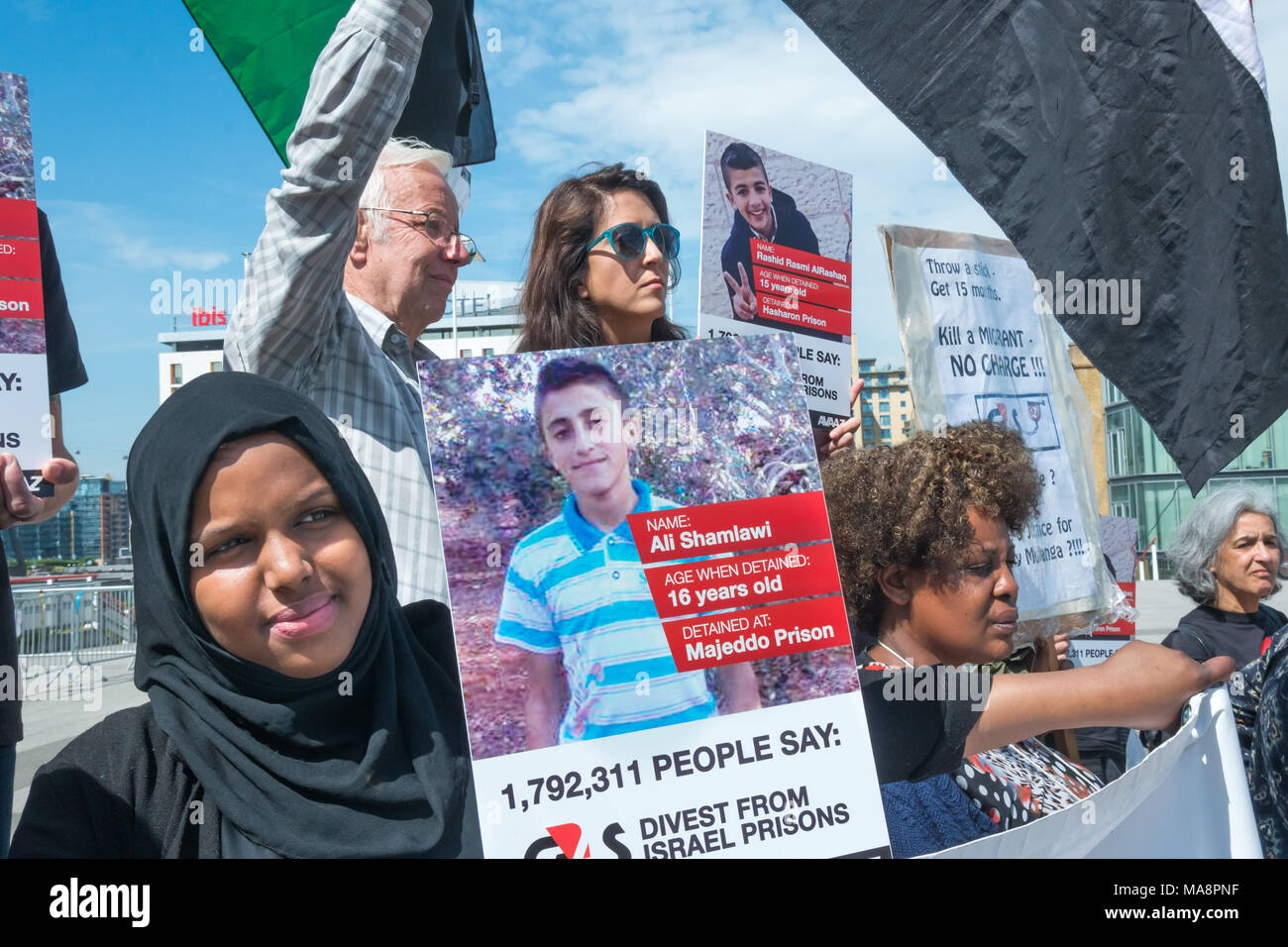 A woman at the Stop G4S protest outside G4S AGM at Excel London holds an Avaaz poster of Ali Shamlawi, detained at 16 and held in Majeddo Prison. 1,792,311 people signed the Avaaz petition calling on G4S to stop running Israeli prisons. Stock Photo