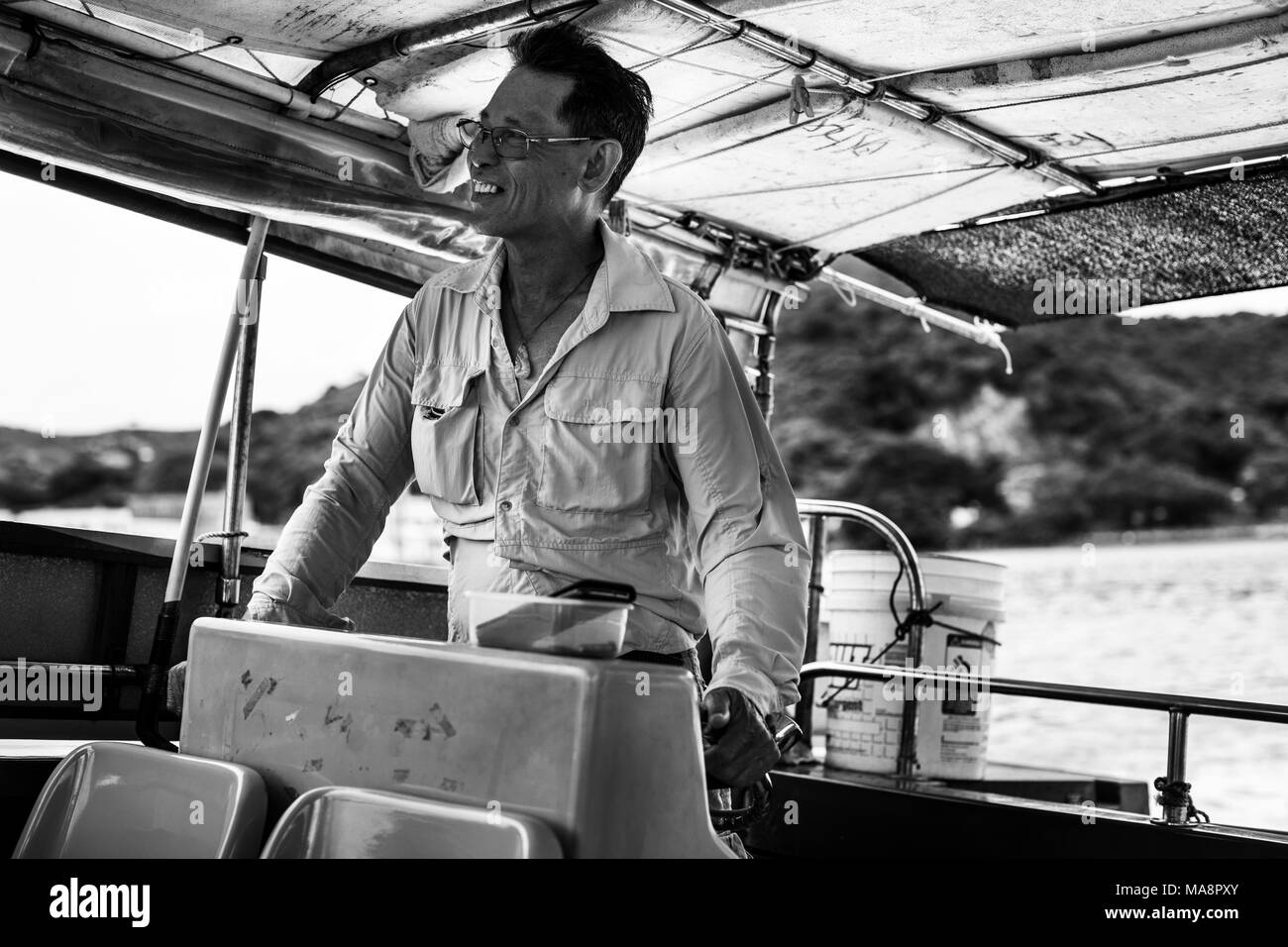 A man drives a tourist boat to look for white dolphins from the fishing village of Tai O, Hong Kong - Stock Image