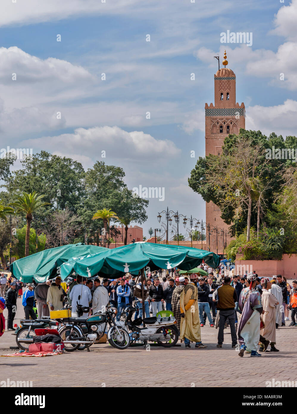 MOROCCO MARRAKECH ENTERTAINERS AND CROWDS PLACE JEMAA EL FNA AND THE KOUTOUBIA TOWER - Stock Image