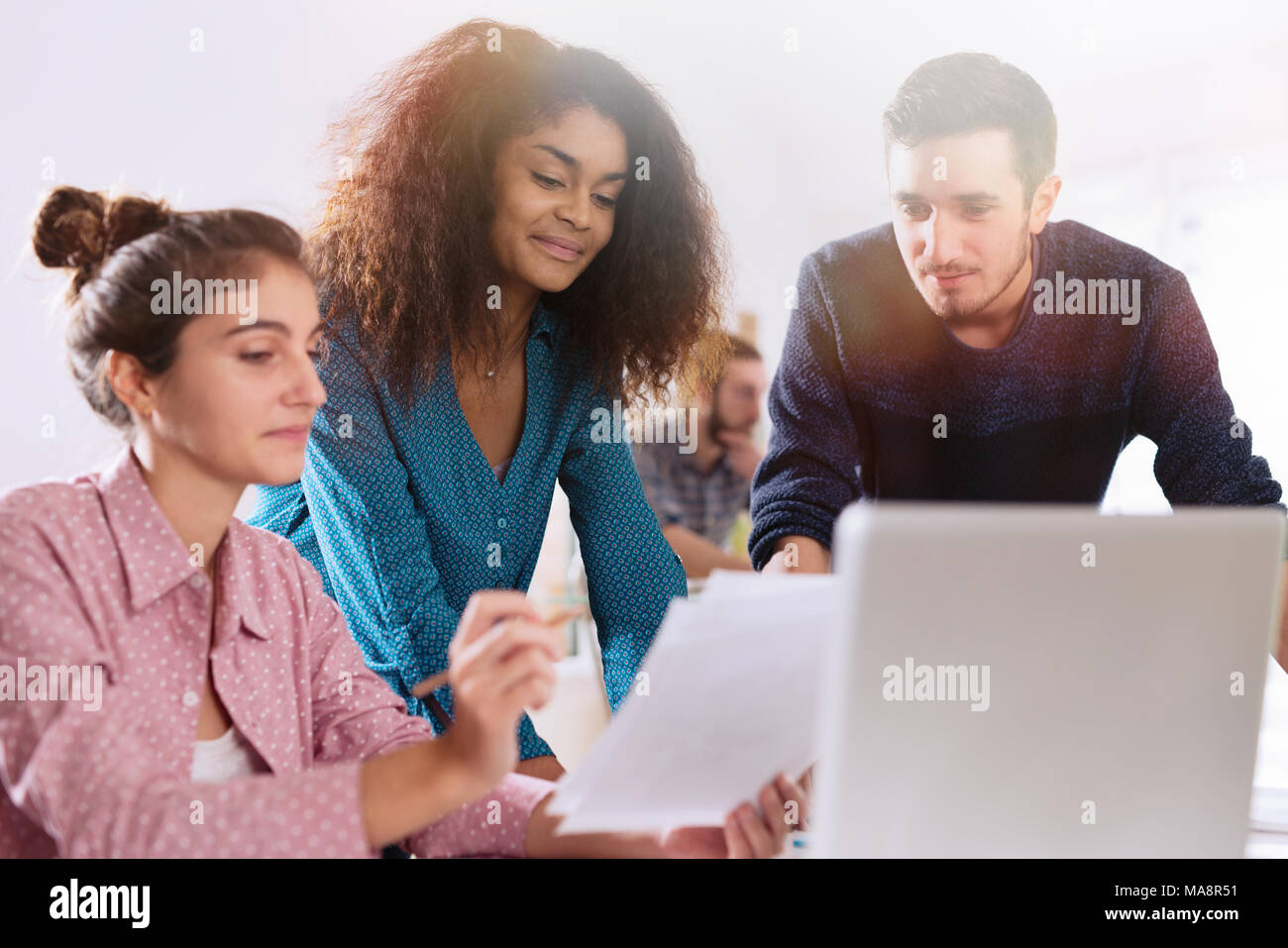 At office. A young multi-ethnic work team exchanges ideas ar - Stock Image