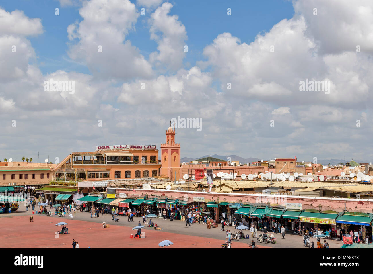 MOROCCO MARRAKECH PLACE JEMAA EL FNA STALLS SHOPS ENTERTAINERS CROWDS PART THREE - Stock Image