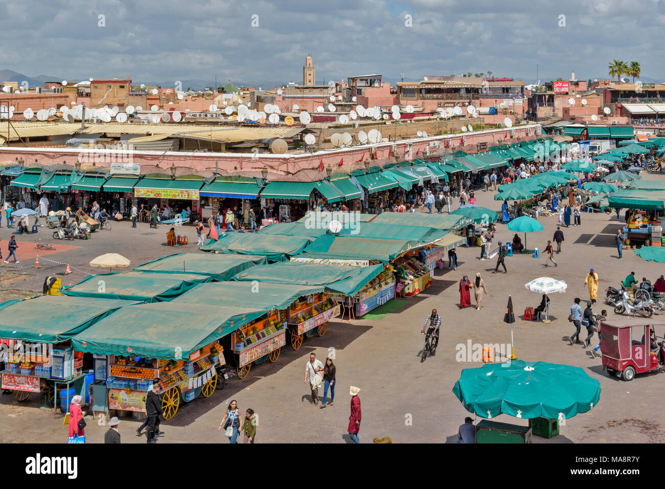 MOROCCO MARRAKECH PLACE JEMAA EL FNA STALLS SHOPS ENTERTAINERS CROWDS PART TWO - Stock Image