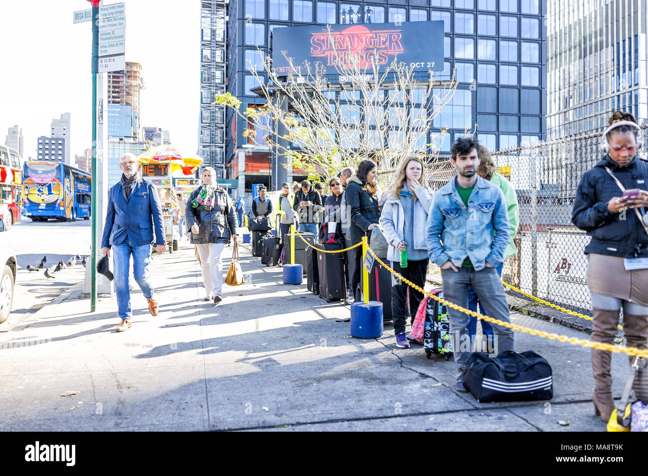 New York City, USA - October 30, 2017: People waiting by MegaBus sign in NYC Manhattan Hudson Yards for buses line queue, sidewalk Stock Photo