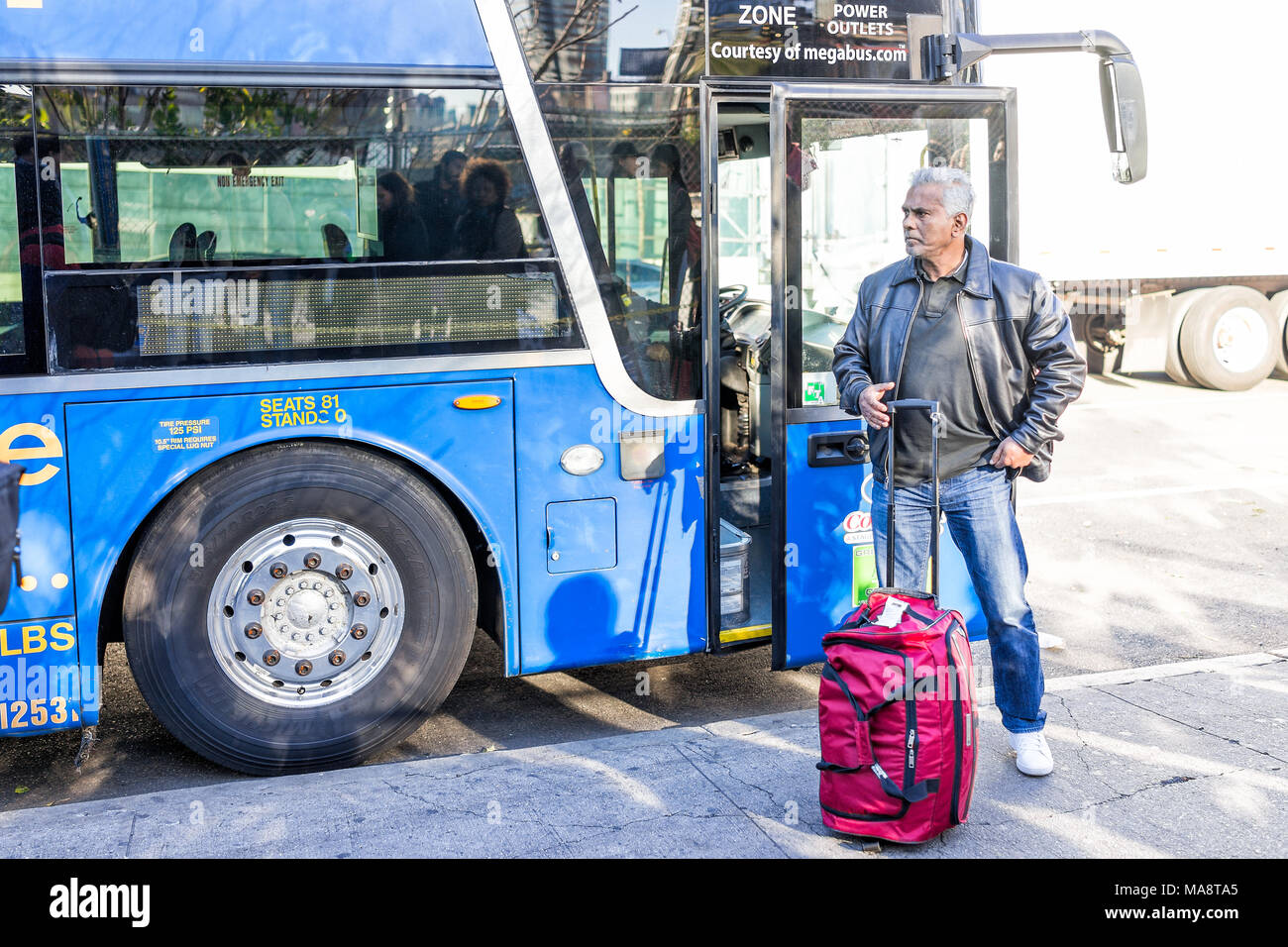 New York City, USA - October 30, 2017: People person one man standing waiting by MegaBus bus sign door in NYC Manhattan Hudson Yards Stock Photo