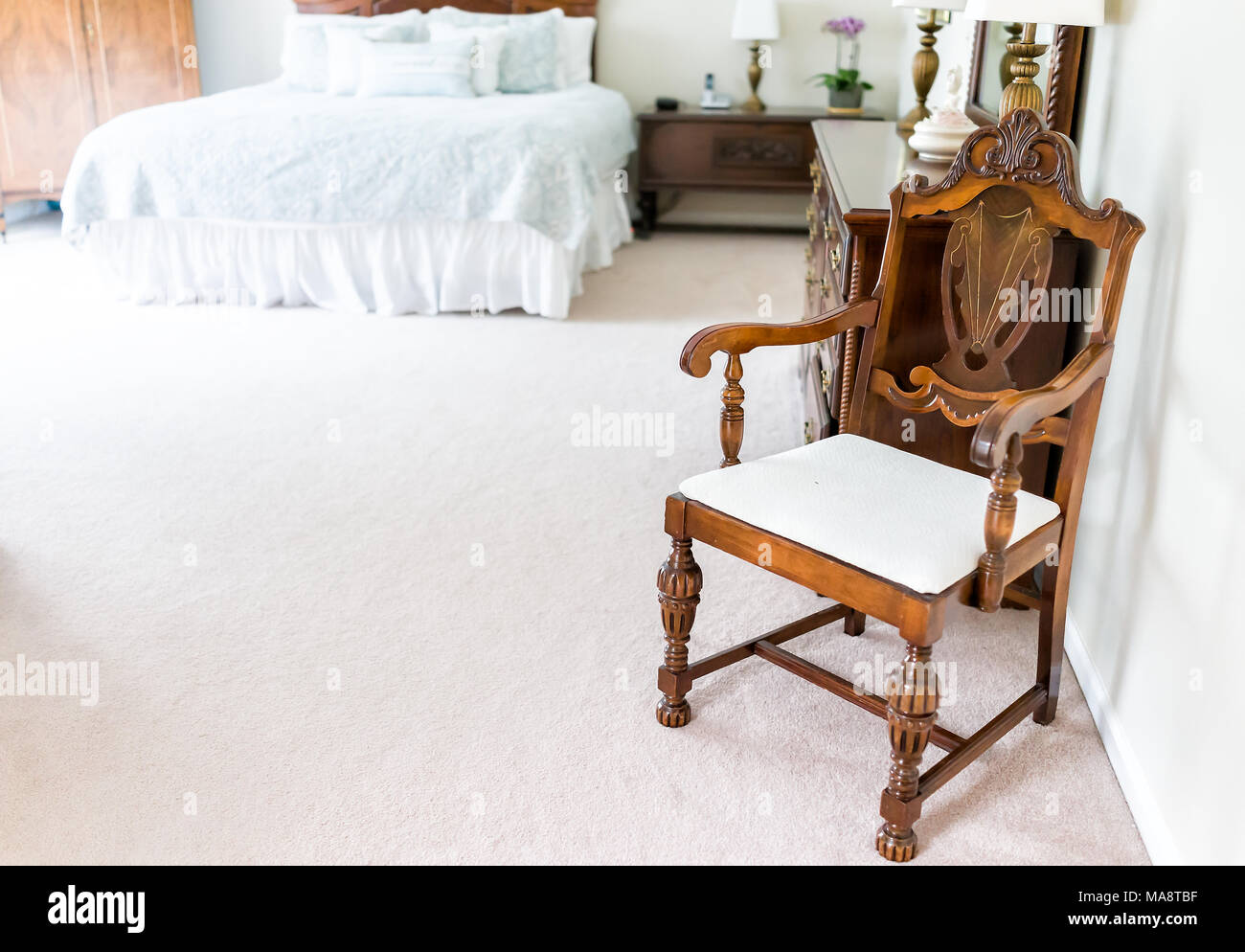 Bright white modern wooden rocking chair in nursery room bedroom with chest of drawers, bed, decorations in model staging home, apartment or house - Stock Image