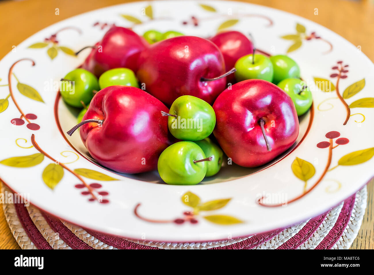 Closeup of colorful decorative plate with fake red green apples pile on kitchen dining table in staging model apartment home & Closeup of colorful decorative plate with fake red green apples ...