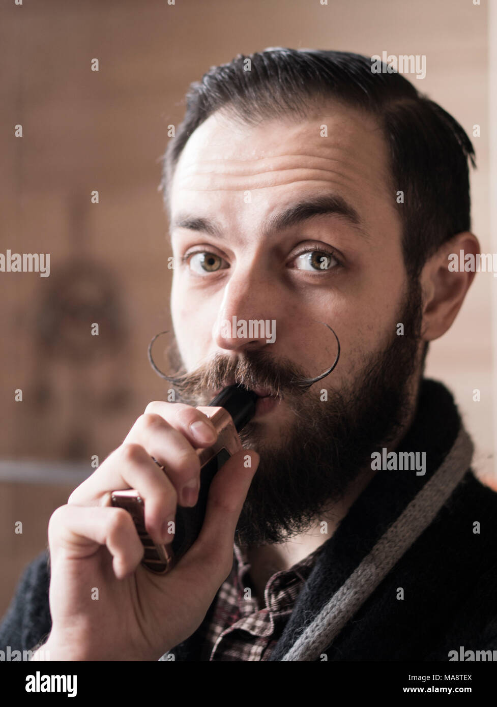 Man with Beard and Mustages Vaping an Electronic Cigarette. Vaper Hipster Smoke Vaporizer in the Room. - Stock Image