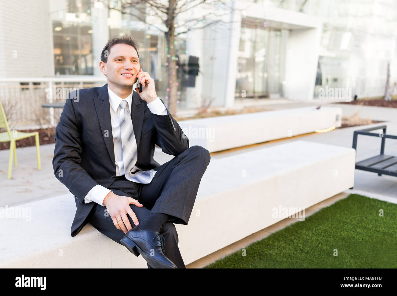 Handsome, attractive young businessman sitting on bench, using talking holding smartphone phone mobile cellphone smiling in suit and tie, cheerful on  - Stock Image