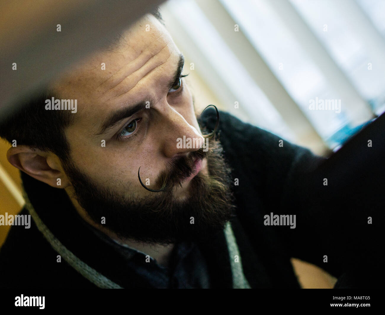 Modern, Expressive Bearded Office Clerk with Mustages Bored to Work in Office - Stock Image
