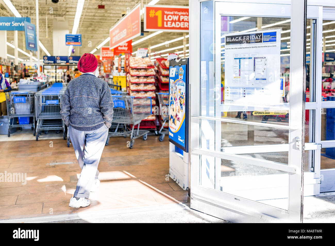 Burke, USA - November 24, 2017: Black Friday sign in Walmart store entrance with map after Thanksgiving shopping consumerism in Virginia with sikh man - Stock Image