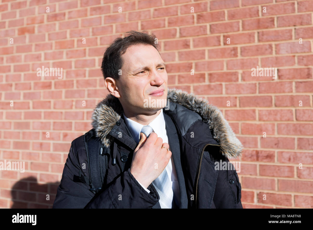 Handsome, attractive young serious unhappy stern businessman closeup face portrait standing in front of brick wall, fixing tie, in suit and tie on int - Stock Image
