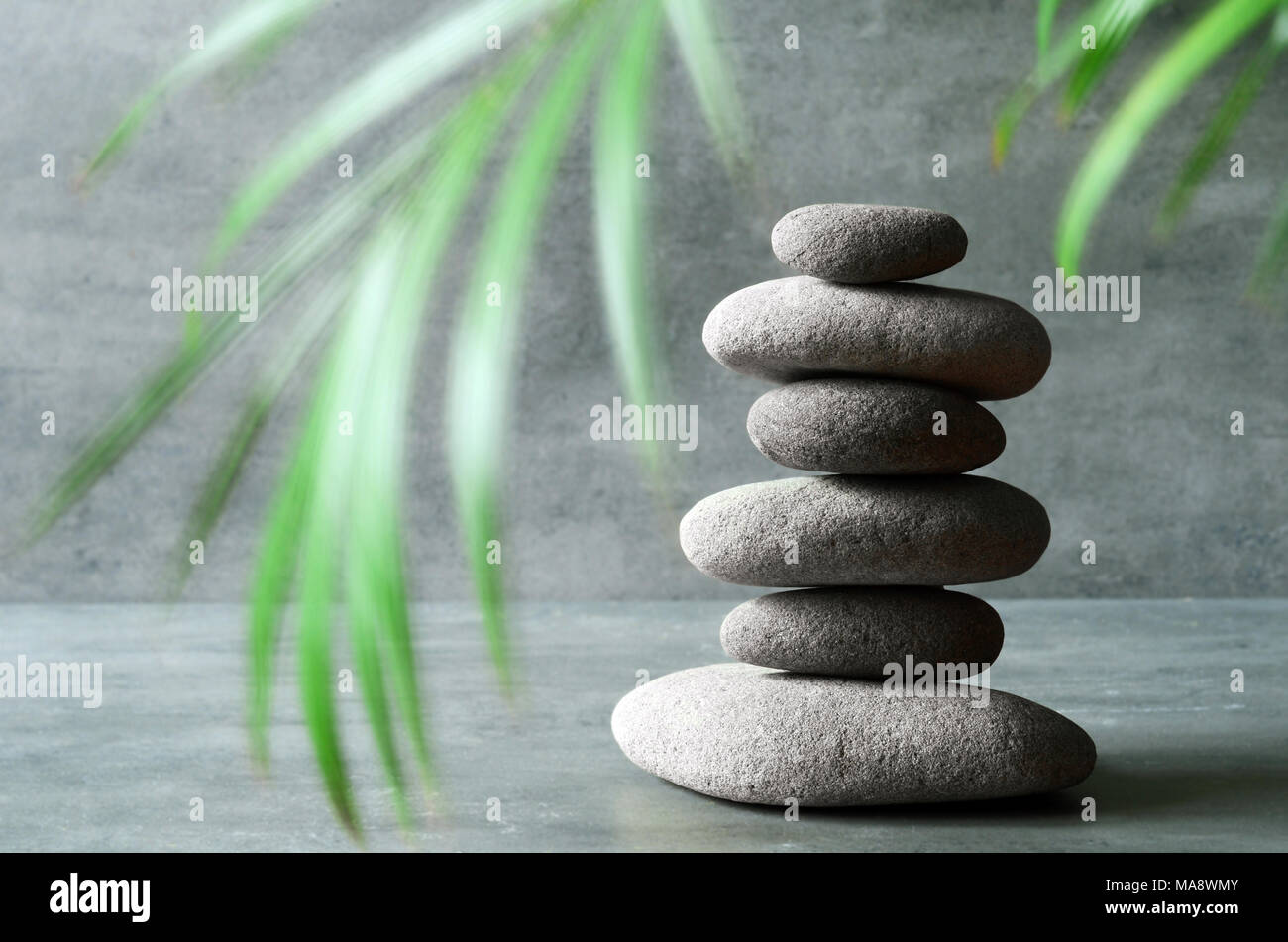 Stones and green palm leaf balance. Zen and spa concept. - Stock Image