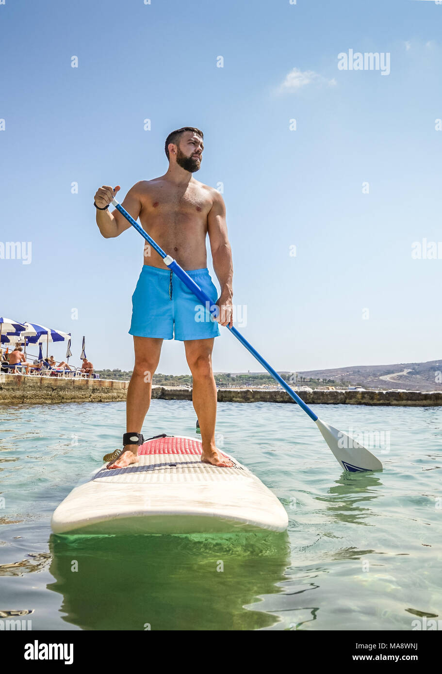 Man paddling on Sup board in blue sea. Beginner paddler Summer active vacation and water sport concept - Stock Image